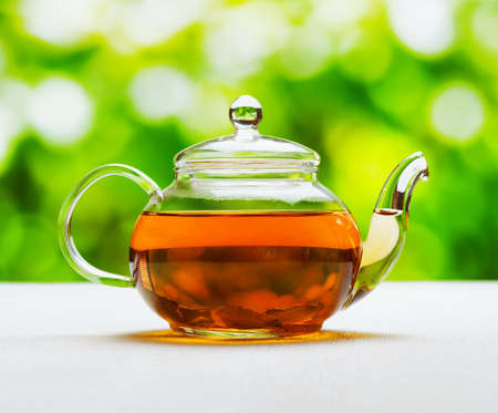 Teapot of fresh tea on natural background. Stock Photo - 22730672