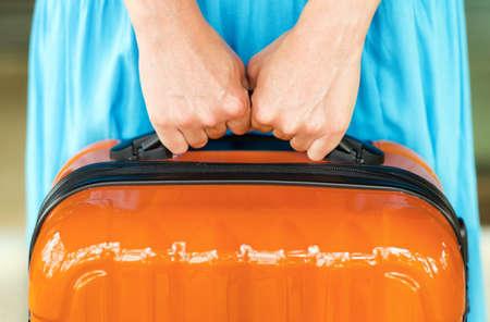femme valise: Femme en robe bleue d?tient valise orange dans les mains.