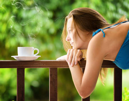 sexy food: Young woman drinking cofee in a garden. Outdoors portrait. Stock Photo