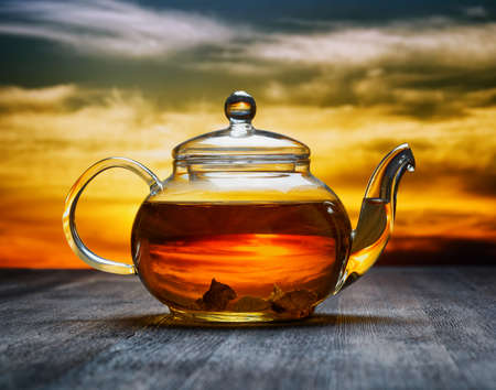 yellow tea pot: Teapot of fresh tea on sky . Stock Photo