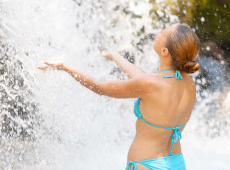 Young woman relaxing in waterfall. photo