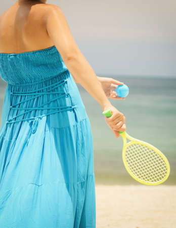Woman in blue dress playing tennis on the beach. photo