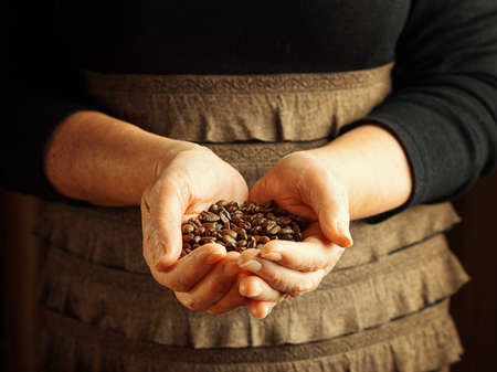 Senior woman holding coffee beans  photo