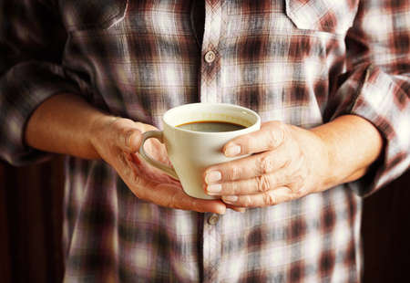 Hands of senior woman holding cup of coffee  photo