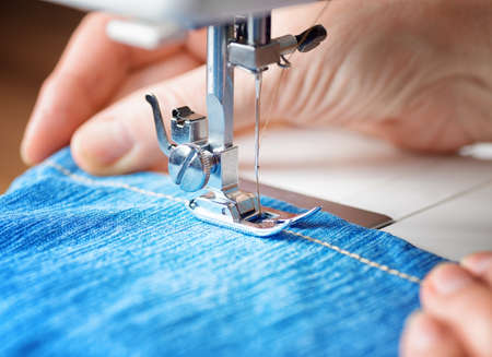 Sewing machine and blue jeans fabric. Zdjęcie Seryjne