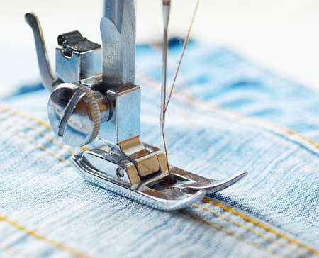 Sewing machine and blue jeans fabric. photo