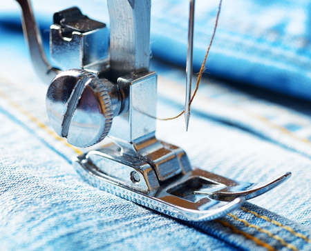 Sewing machine and blue jeans fabric. Stock Photo