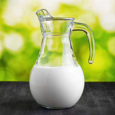 milk jug: Jug of milk on nature background. Half full pitcher. Stock Photo