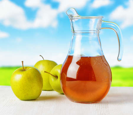 Jug of apple juice on nature background. Half full pitcher. photo