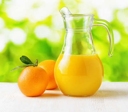 Jug of orange juice on nature background. Half full pitcher. photo