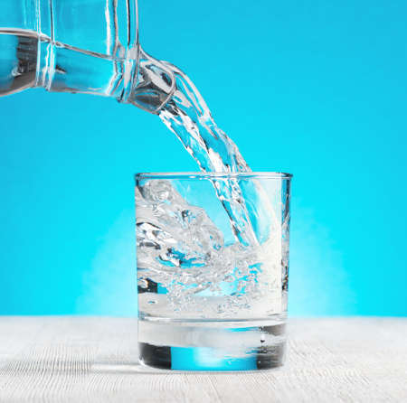 Water pouring into a glass on blue background. photo