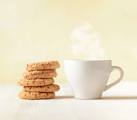 oatmeal cookie: Oatmeal cookies and cup of coffee on wooden table. Stock Photo