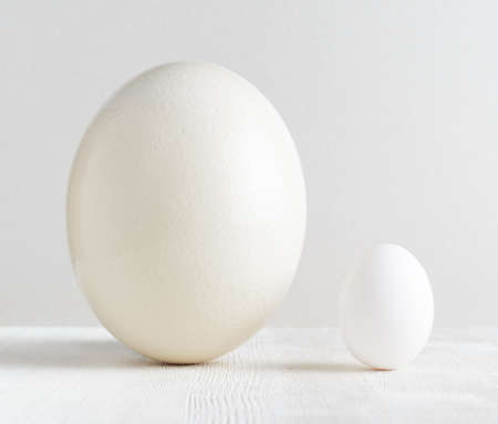 Ostrich egg and chicken egg on white table. photo