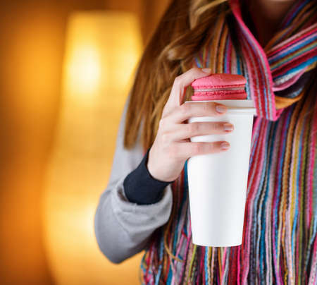 Young woman holding a tumbler of coffee in cafe. photo