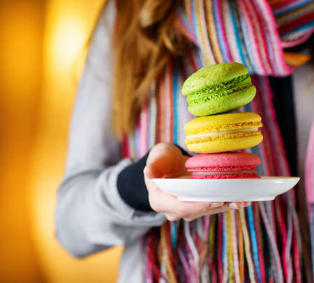 Young woman holding the french pastry macaron in cafe  photo