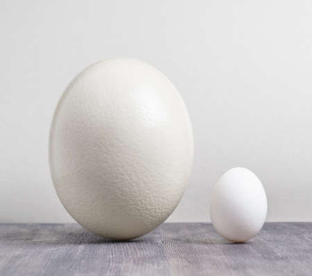 Ostrich egg and chicken egg on black table. photo