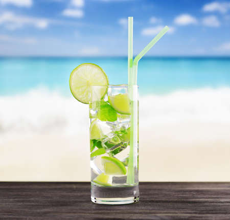 Glass of mojito cocktail on a beach. photo