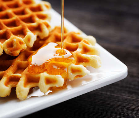 syrup: Honey pouring on a fresh waffles. Stock Photo