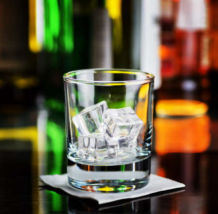 Glass with ice cubes on a bar desk. photo
