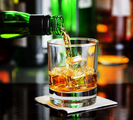 a shot: Whiskey pouring a glass in a bar.