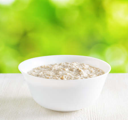 Bowl of oat porridge on nature background. photo