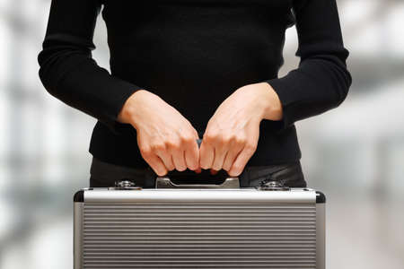 business briefcase: Business woman holding an aluminium briefcase. Stock Photo