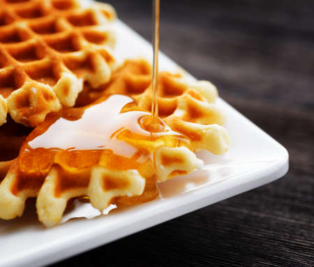 Honey pouring on a fresh waffles. Stock Photo