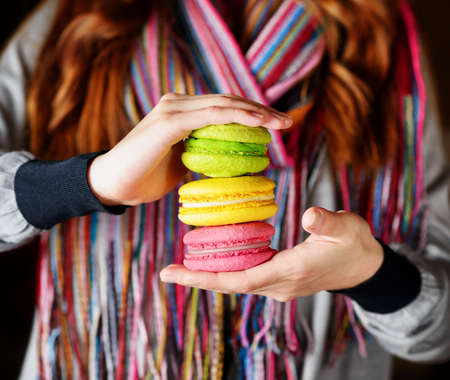 Young woman holding the french pastry macaron in cafe. photo