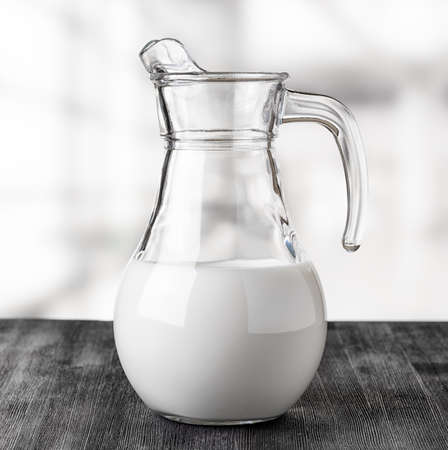 Jug of milk on the factory background. Half full pitcher. photo