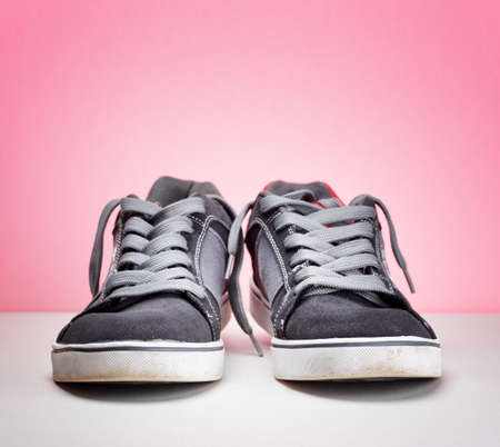 Pair of grey sneakers on colorful wall. photo