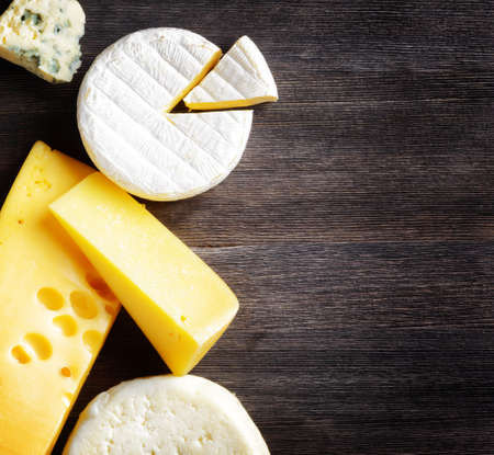 Different types of cheese on a wooden board.