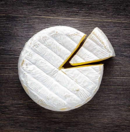 Camembert cheese on a wooden board.