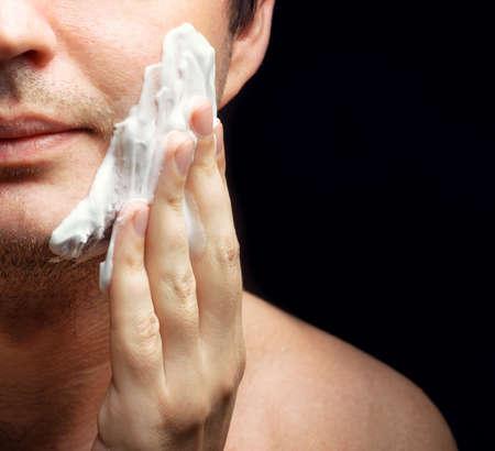 Young man applying a shaving foam. Skin protection. photo