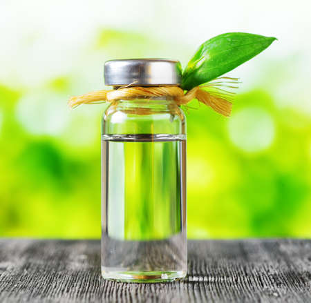 Vial of liquid on nature background  Aromatherapy and natural medicine
