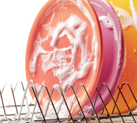 Plates with cleaning foam in dishwasher. photo