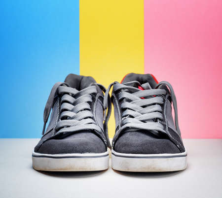 Pair of grey sneakers on colorful . photo