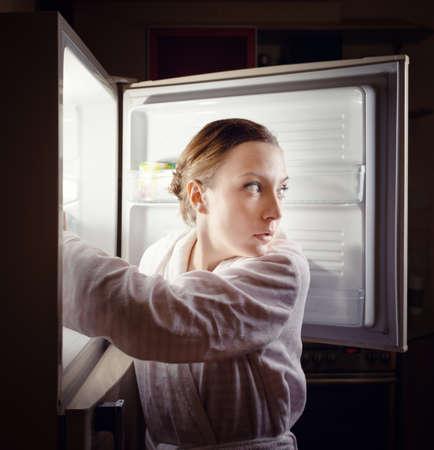 若い女性が夜遅くに冷蔵庫の中にいくつかのスナックを探してします。