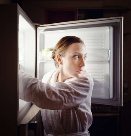 refrigerador: Mujer joven en busca de un bocadillo en la nevera durante la noche. Foto de archivo