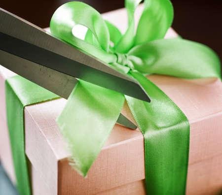 Decorating gift box with green ribbon using scissor  photo