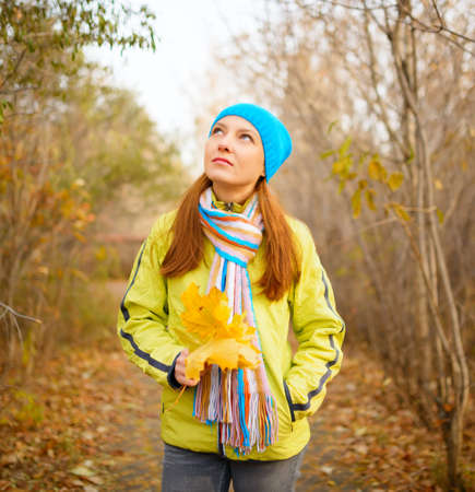 Young woman walking in the fall season. Autumn outdoor portrait. photo