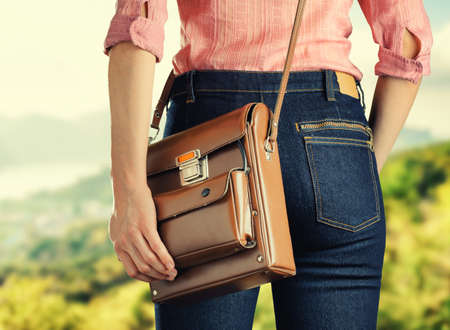 Young woman in deep blue jeans holding a bag. Retro style. photo