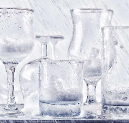 lavar trastes: Lavado de cristalería bajo chorros de agua.