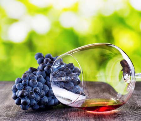 나무 테이블에 포도와 와인 유리입니다.