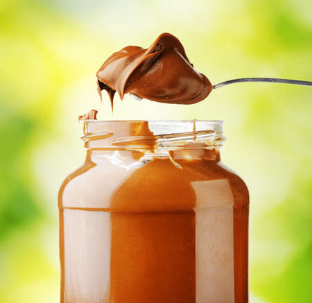 A jar of hazelnut chocolate spread on nature background.