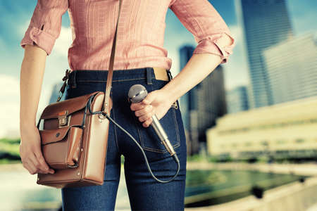Female journalist with microphone. Retro style jeans and bag. photo