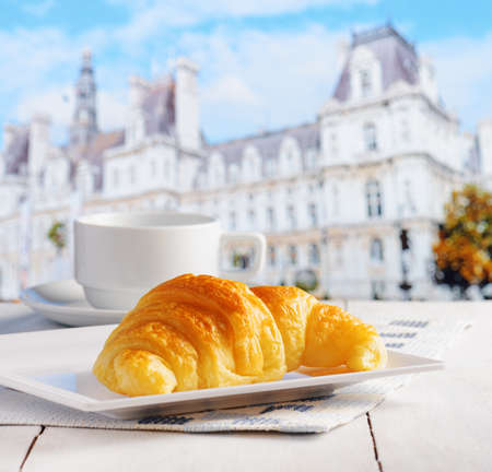 Cup of coffee and croissant on a table in a european street cafe. photo