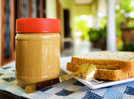 Jar of peanut butter and toasts on summer terrace. photo