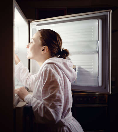 beverage fridge: Young woman looking for some snack in fridge late at night.