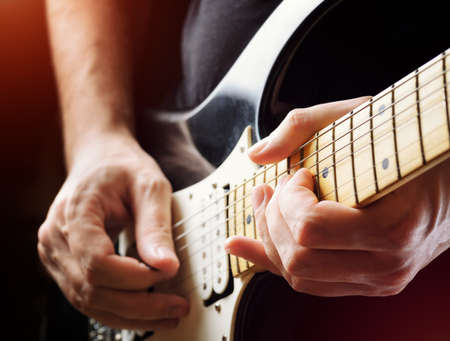 electric guitar: Man playing guitar on a stage. Musical concert. Close-up view.