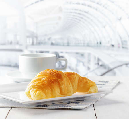 Cup of coffee and croissant in cafe. photo